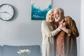 happy senior couple dancing at home and looking away
