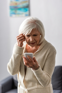 thoughtful senior woman touching head while using smartphone at home
