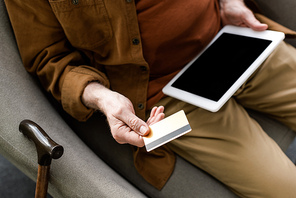 cropped view of senior man holding digital tablet with blank screen and credit card