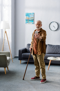 happy senior man standing with walking stick and taking selfie on smartphone