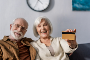 selective focus of happy senior woman showing credit card near smiling husband