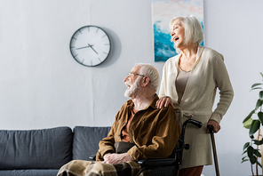 senior woman and handicapped husband in wheelchair laughing while looking away