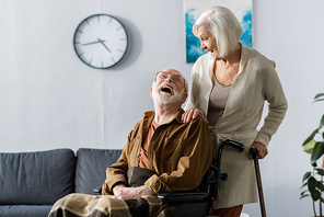 senior wife and cheerful husband in wheelchair laughing while looking at each other
