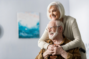 cheerful senior woman embracing happy disabled husband