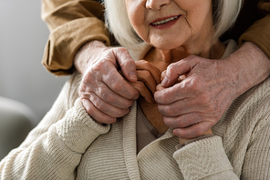 partial view of senior man holding hands of smiling wife