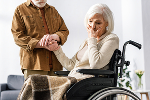 cropped view of man holding hand of disabled wife, sick on dementia, holding hand on face while sitting in wheelchair