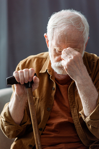 senior, lonely man touching face while sitting with walking stick