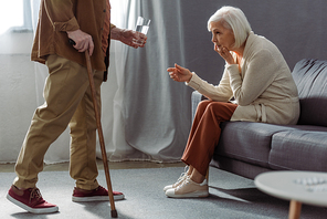 cropped view of senior man giving glass of water to wife feeling bad and sitting on sofa