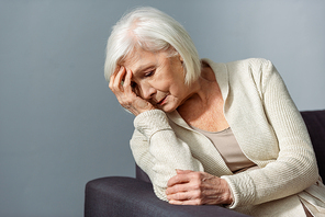 senior lonely woman holding hand on face while sitting on sofa