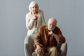 depressed senior woman touching chest while standing behind husband, sick on dementia