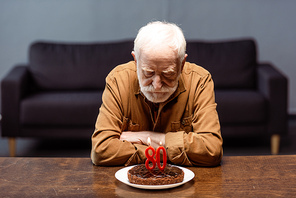 senior lonely man sitting with crossed arms near birthday cake with number eighty