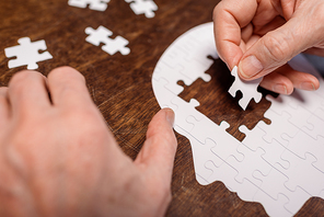 cropped view of sick senior man combining jigsaw puzzle for dementia therapy