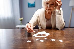 senior woman combining jigsaw puzzle for dementia rehabilitation