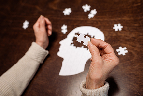 cropped view of woman colleting jigsaw puzzle as dementia therapy