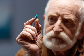 selective focus of senior man looking at pill in his hand
