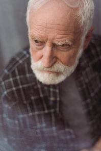 selective focus of depressed senior man looking away through window glass