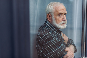 senior, upset man standing with crossed arms and looking away through window glass