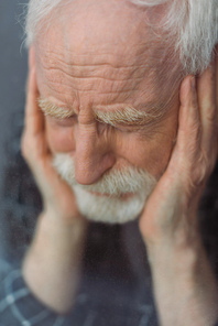 selective focus of senior, depressed man with closed eyes touching face near window glass
