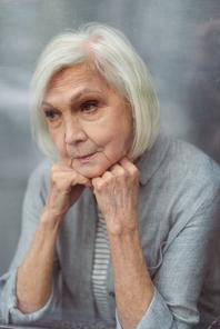 sad senior woman looking away through window glass