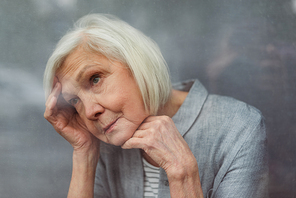 lonely senior woman loooking away while standing by window