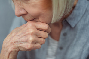 cropped view of senior lonely woman holding hand near chin