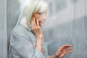 depressed senior woman touching face and window glass while looking away