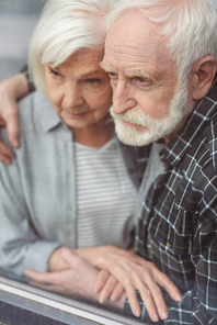 thoughtful senior man and his wife, sick on dementia, holding hands while standing by window