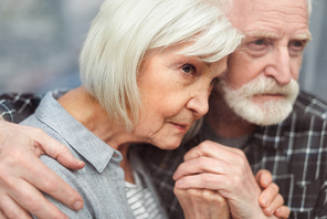 thoughtful senior man holding hands of wife, sick in dementia, while looking through window