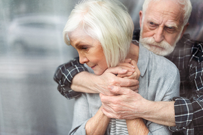 upset senior man hugging wife, sick on dementia, while standing by window