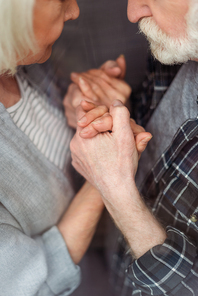 cropped view of senior woman and her husband, sick on dementia, holding hands