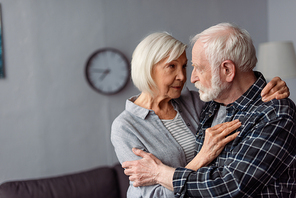 senior woman hugging husband, sick on dementia, while standing face to face