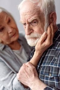 senior woman touching face of husband suffering from dementia