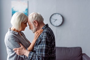 senior woman and husband with dementia hugging while standing face to face