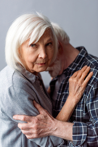 upset senior woman looking at camera while hugging husband suffering from dementia