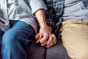 cropped view of senior couple sitting on sofa and holding hands