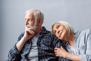 dreamy senior woman leaning on shoulder of thoughtful husband looking away
