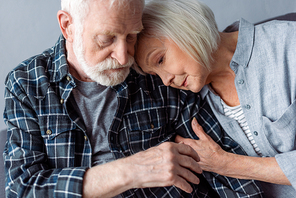 senior woman hugging and leaning on old man with dementia disease