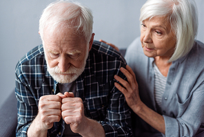 worried senior woman touching husband suffering from dementia and sitting with clenched fists