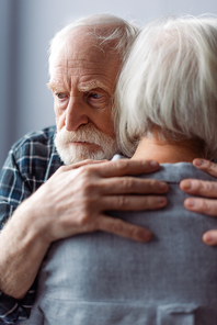 senior man, suffering from dementia, hugging wife and looking away