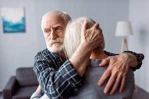 senior, sad man hugging wife, sick on dementia, and looking away