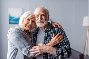 happy senior couple smiling and embracing while looking at camera