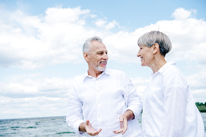 smiling senior man in white shirt lifting wife at beach under blue sky