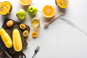 top view of wooden cutting boards with zucchini, apricots, yellow, pumpkin and honey with cutlery on marble surface