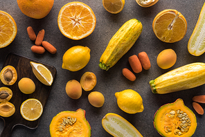 top view of yellow fruits and vegetables on wooden cutting board on grey textured background