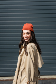 joyful woman in trench coat and beanie hat winking eye