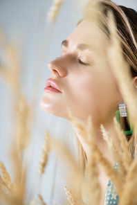 young woman with closed eyes near wheat spikelets on blurred foreground