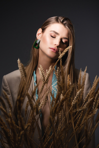 young woman with closed eyes standing near wheat spikelets on dark grey background