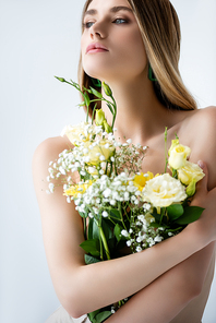 young model with naked shoulders embracing flowers on white