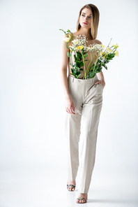 full length of young woman with flowers in pants posing on white