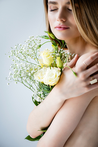 young model with closed eyes embracing flowers on grey